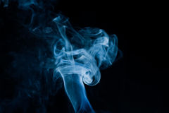 Creative blue smoke on black background Stock Images