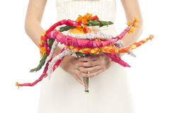 Creative bouquet of multicolored strands. Creative bunch of strands of red, orange, white and green in the hands of the bride. Harnesses are made of flower stock images