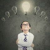 Creative boy with lightbulb over head Stock Images