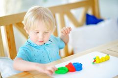 Creative boy playing with colorful modeling clay at kindergarten Stock Photos