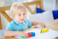 Creative boy playing with colorful modeling clay at kindergarten. Little kid molding at home. Development toys for preschooler children Royalty Free Stock Image