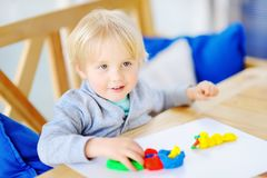 Creative boy playing with colorful modeling clay at kindergarten Stock Images
