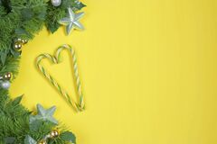 Creative branch of a Christmas tree with New Year`s toys and candy cane on a Illuminating Yellow background. Christmas and New Yea