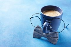 Creative breakfast on Happy Fathers Day with funny face from cup of coffee, eyeglasses and bowtie. Royalty Free Stock Photos