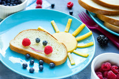 Creative breakfast idea for kids - bread bun with fruit and berr Stock Photography
