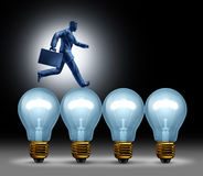 Creative Bridge. Business concept with a man in a suit running on light bulbs using ideas to move forward with innovation and wealth on a black background Royalty Free Stock Photography