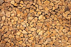 Creative brown background of neatly stacked firewood. Brown texture of natural wood. Creative brown background of neatly stacked firewood. Brown texture of royalty free stock photo