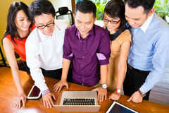 Creative Business Asia - Team Meeting in office. Asian Creative business agency - team meeting in an office with laptop Royalty Free Stock Photography