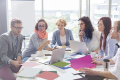 Creative business colleagues analyzing photographs at conference table in office Stock Photo