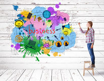 Creative business concept. Side view of young european woman standing on wooden stool and drawing colorful sketch on wooden wall. Creative business concept. 3D Royalty Free Stock Image
