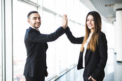 Creative business couple hands up doing high five in office. With panoramic windows Royalty Free Stock Image