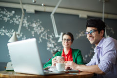 Creative Business People in Cafe with Laptop. Portrait of two young creative colleagues men and women both wearing casual clothes and glasses, working at meeting Royalty Free Stock Images