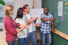 Creative business people clapping hands by blackboard Royalty Free Stock Images