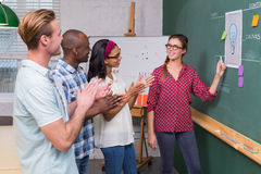 Creative business people clapping hands by blackboard Stock Photo