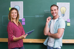 Creative business people with digital tablet by blackboard Royalty Free Stock Photos