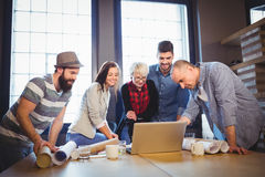 Creative business people discussing over laptop Royalty Free Stock Images