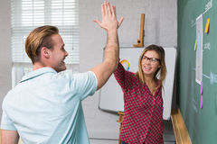 Creative business people high fiving by blackboard Stock Photos