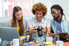 Creative business people looking at digital camera at desk Royalty Free Stock Image