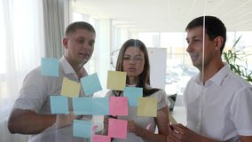 Creative business people with many sticky notes to window in boardroom. Creative business people with many sticky notes to window working on new project in stock footage