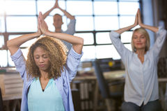 Creative business people practicing yoga. In office Stock Photo