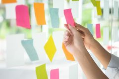 Creative business people reading sticky notes on glass wall with. Colleague working use post it notes to share idea discussing and teamwork, brainstorming royalty free stock photo