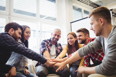 Creative business people stacking hands in meeting room. Smiling creative business people stacking hands in meeting room at office Stock Image