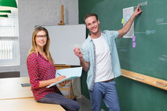 Creative business people at work against blackboard Stock Images