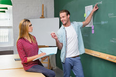 Creative business people at work against blackboard Stock Photography