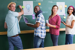 Creative business people at work by blackboard Royalty Free Stock Images