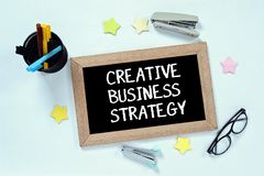 CREATIVE BUSINESS STRATEGY word on top view of blackboard with glasses, pen case, staplers and marker royalty free stock photo