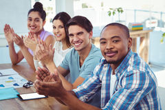 Creative business team applauding at meeting Stock Photography