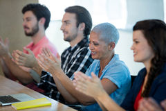Creative business team applauding in meeting room Stock Image