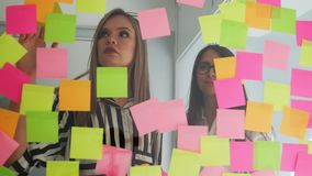 Creative business team brainstorming ideas working together sharing data late at night after hours in modern glass. Office. Two very beautiful girls in office stock video footage