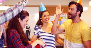 Creative business team celebrating their colleagues birthday. In office stock footage