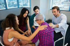 Creative business team consoling upset colleague royalty free stock photography