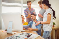 Creative business team discussing over a tablet Royalty Free Stock Image