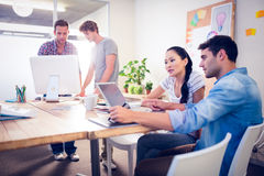 Creative business team gathered around laptops Royalty Free Stock Images