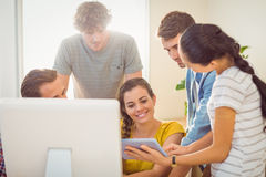 Creative business team gathered around a tablet Stock Photography