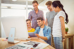 Creative business team gathered around a tablet Royalty Free Stock Images