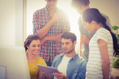 Creative business team gathered around a tablet Stock Images