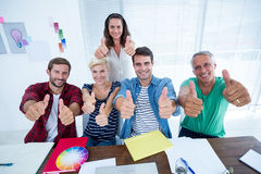 Creative business team gesturing thumbs up in meeting Royalty Free Stock Images