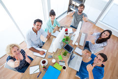 Creative business team gesturing thumbs up in a meeting Royalty Free Stock Images