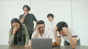 Creative business team getting very bad news on his laptop. Casual creative business team getting very bad news on his laptop computer screen and feeling stock video footage