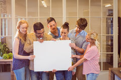 Creative business team holding cardboard written Stock Image