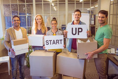Creative business team holding cardboard written start up Stock Image