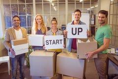Creative business team holding cardboard written start up Stock Image