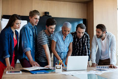Creative business team looking at presentation in laptop Stock Image