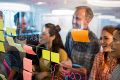 Creative business team looking at sticky notes on glass window Royalty Free Stock Images