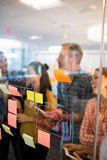Creative business team looking at sticky notes on glass window Stock Image