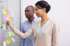 Creative business team looking at sticky notes on window Stock Image